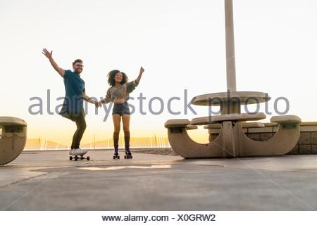 Couple using rollerskates and skateboard, holding hands, smiling - Stock Photo