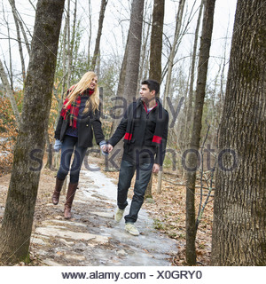 A couple walking hand in hand through a woodland in winter. - Stock Photo