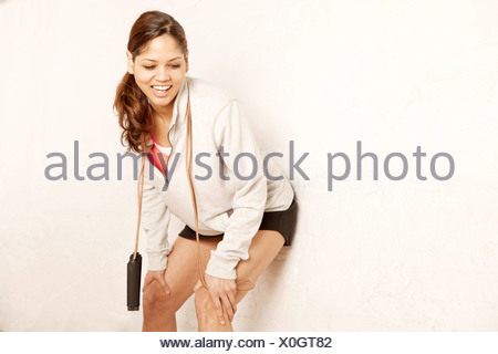 Young woman leaning against wall - Stock Photo