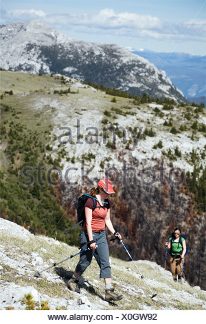 Two women hike on a broad ridge in the southern Chilcotin mountains. - Stock Photo