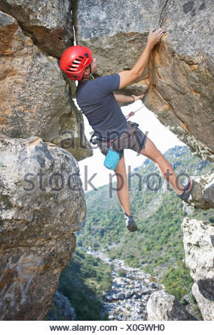 Young male rock climber balancing and holding rope