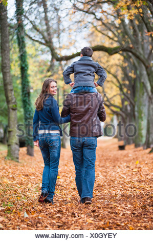 Parents and young son strolling through autumn leaves in park - Stock Photo
