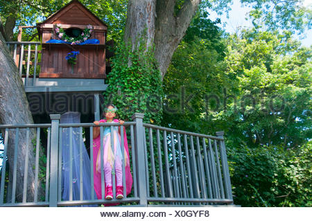 Young girl wearing fancy dress costume, standing in tree house - Stock Photo