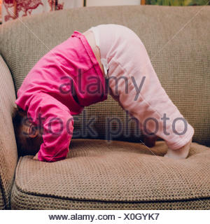 Side View Of Baby Girls Doing Headstand On Sofa At Home - Stock Photo