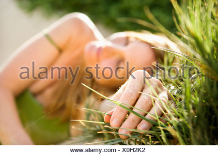 Selective focus portrait of young woman relaxing in grass - Stock Photo