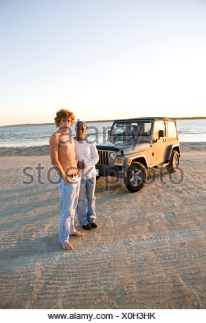 Young interracial couple standing on beach in front of jeep - Stock Photo
