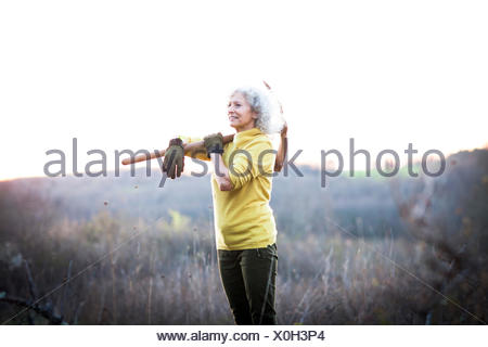 Mature woman carrying pick axe over her shoulder in landscape - Stock Photo