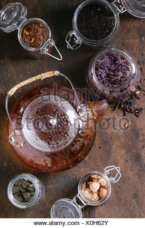 Variety of black, green and herbal dry tea leaves in glass jars with vintage strainer and teapot of hot tea over old dark wooden background. Top view - Stock Photo