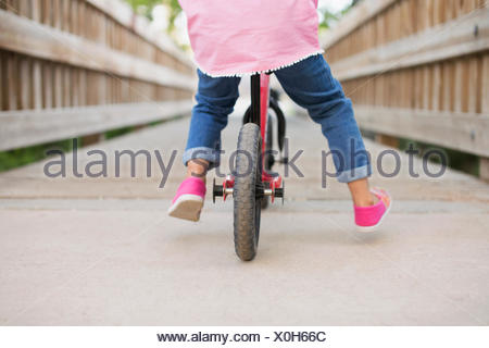 A child riding on a bicycle on a boardwalk.