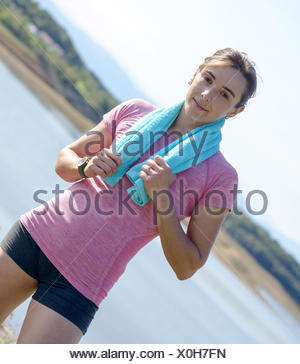 young sporty woman with blue towel in the countryside - Stock Photo