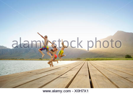Family, in swimwear, jumping into a lake from a jetty - Stock Photo