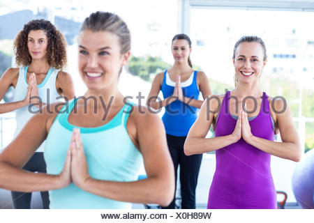 Women smiling in fitness studio with hands together - Stock Photo