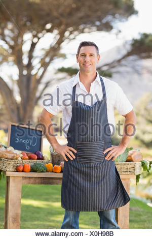 Smiling farmer standing with hands on hips - Stock Photo