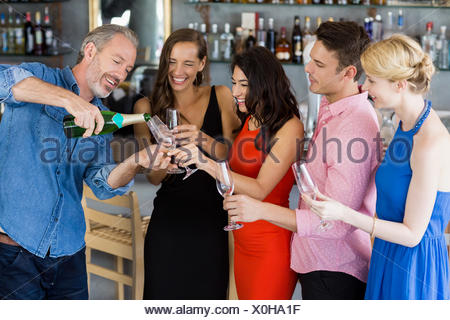 Man pouring champagne into glass - Stock Photo