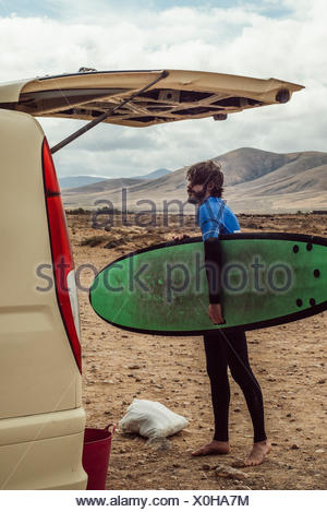 Young surfer holding green surfboard in desert - Stock Photo