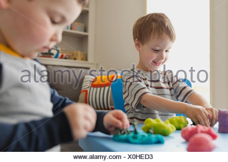 Boys playing with play dough - Stock Photo