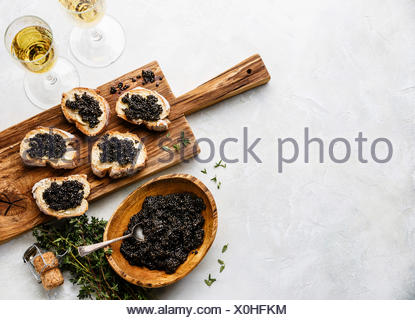 Sturgeon black caviar in wooden bowl, sandwiches and champagne on white background copy space - Stock Photo