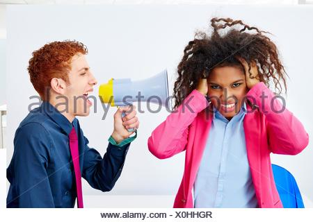 businessman talking in megaphone to african executive with scared expression. - Stock Photo