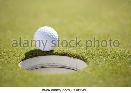 Close-up of a golf ball on the edge of a hole - Stock Photo
