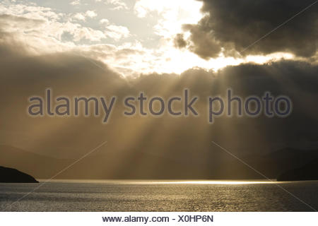 Sunrays break through the thick cloud cover on the north coast of the south island of New Zealand and makes the sea glittering - Stock Photo