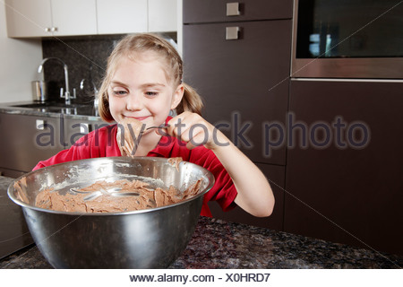 Girl eating cake mix from the bowl - Stock Photo