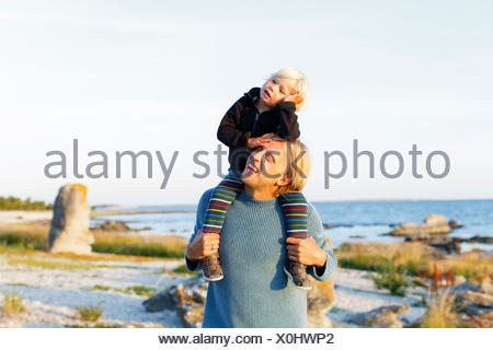 Sweden, Gotland, Farosund, Father carrying on shoulders little son (2-3) - Stock Photo