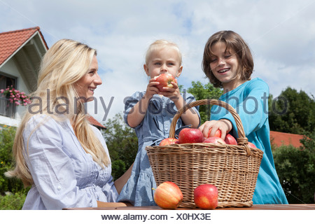 Germany, Munich, Mother with children eating apples from basket - Stock Photo