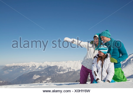 Couple and daughter in ski wear, looking away - Stock Photo