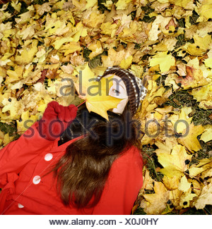 Portrait of a young woman holding a maple leaf - Stock Photo