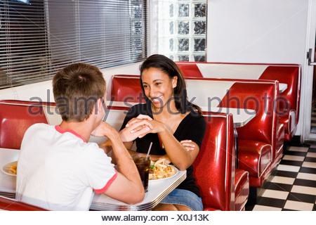 Teenage interracial couple having lunch in a retro diner - Stock Photo
