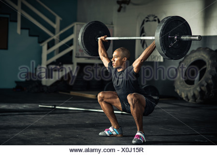 Young man weightlifting barbells in gymnasium - Stock Photo