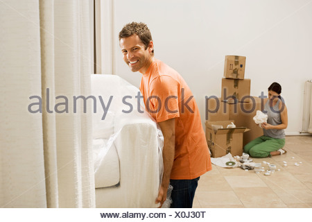 Couple moving house man lifting white sofa through doorway woman packing boxes in sparse room - Stock Photo