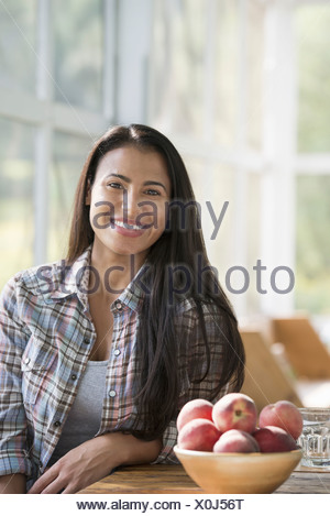 A happy young woman sitting at a table. - Stock Photo
