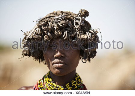 Tribal woman wearing hat made out of bottle lids. - Stock Photo