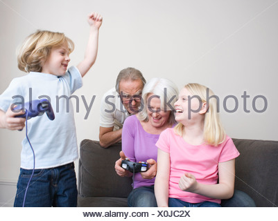 Grandparents and grandchildren (8-9) playing video game, portrait - Stock Photo