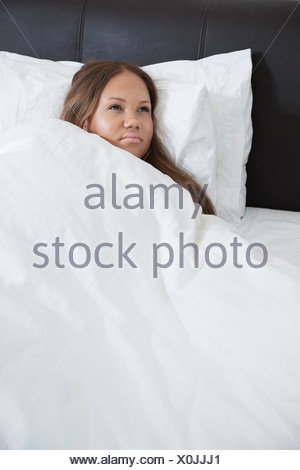 Thoughtful young pregnant woman lying in bed - Stock Photo