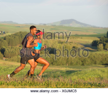 Man and woman running in landscape, Othello, Washington, USA - Stock Photo