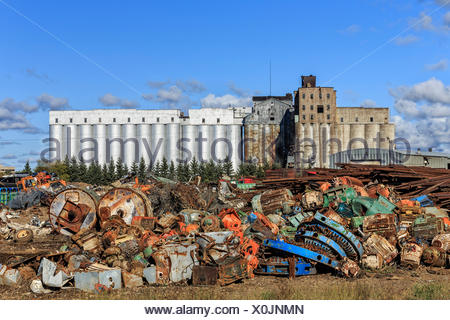 Scrap metal recycling, with an abandoned grain elevator in background, Thunder Bay, Ontario, Canada. - Stock Photo