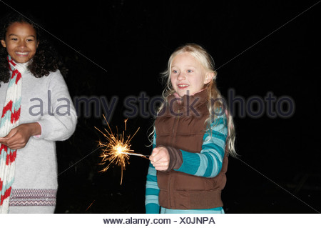 Two young girls with sparklers - Stock Photo