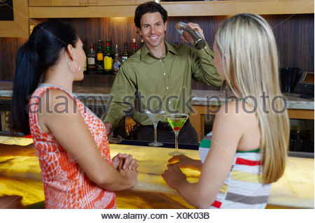Bartender Mixing Drinks for Women at Bar - Stock Photo