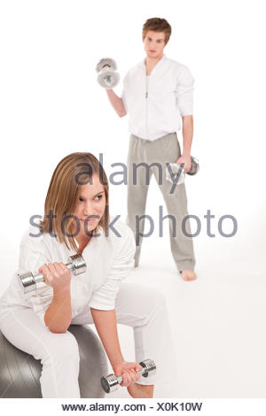 Fitness - Young couple training with weights and ball - Stock Photo