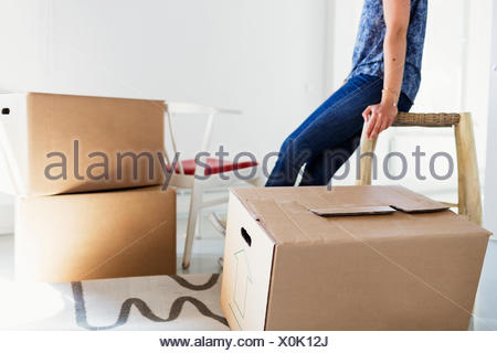 Midsection of woman sitting on table by boxes in new home - Stock Photo