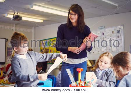 Female teacher with children drawing in elementary school classroom - Stock Photo