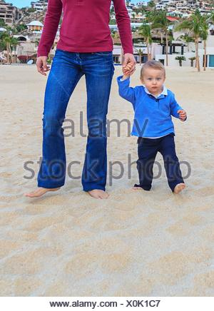 Mother and son on beach, holding hands, low section - Stock Photo
