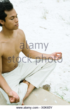 Barechested man sitting in lotus position, eyes closed, cropped - Stock Photo
