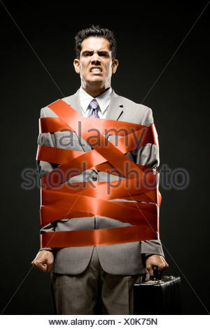 businessman wrapped up with red tape - Stock Photo