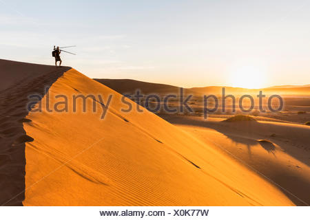 Namibia, Namib Desert, Namib Naukluft National Park, photographer standing on dersert dune - Stock Photo