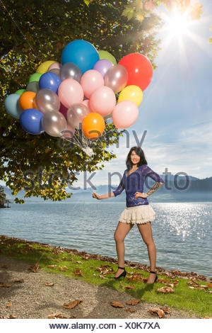 Young woman in blue top and white short skirt posi - Stock Photo