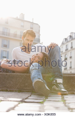Woman lying on lap of a man at the ledge of a canal, Paris, Ile-de-France, France - Stock Photo