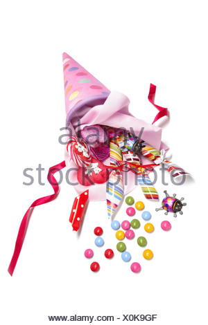 Pink schultuete or school cone with sweets spilling out - Stock Photo